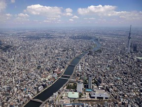 TOPSHOT - This aerial photo shows the Sumida river and the city skyline in Tokyo, ahead of the Tokyo 2020 Olympic Games, July 19, 2021.