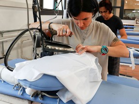 FILE PHOTO: A woman works at the Brunello Cucinelli factory in Solomeo village, near Perugia, Italy, September 4, 2018.