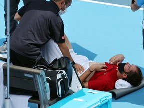 Russia's Daniil Medvedev is assisted by a physio during Tokyo 2020 Olympic Games men's singles third round tennis match.