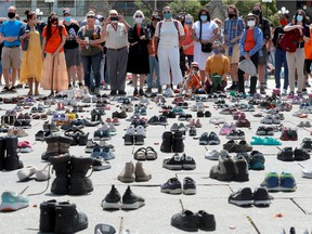 Standing behind the hundreds of little shoes that represented the original 215 children found buried at a residential school, people listen to the speakers on Parliament Hill before a march in downtown Ottawa this past summer.