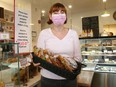 Sophie Gourves, co-owner of Mamie Clafoutis French bakery in Westboro, stands near her front counter, which is covered with plexiglass and has clear signs about vaccine passports being required for indoor dining.