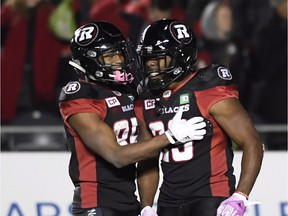 The Redblacks' Diontae Spencer, left, and William Powell celebrate a touchdown against the Ticats in the regular-season finale on Oct. 27. THE CANADIAN PRESS/Justin Tang