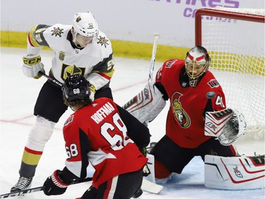Vegas Golden Knights left wing Tomas Nosek (92) and Ottawa Senators goalie Craig Anderson (41) keep their eyes on a flying puck as left wing Mike Hoffman (68) looks on.
