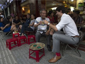 Canadian Prime Minister Justin Trudeau speaks with Nguyen Cong Hiep as the two stop for a drink at local cafe in Ho Chi Minh, Vietnam Thursday November 9, 2017. The PM, since he's abroad, won't be at Saturday's Remembrance Day ceremony. THE CANADIAN PRESS/Adrian Wyld