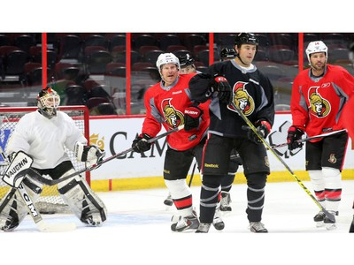 The two captains of the upcoming game, Chris Phillips and Daniel Alfredsson, watch for the puck.