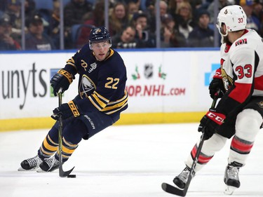 Johan Larsson #22 of the Buffalo Sabres skates up ice with the puck as Fredrik Claesson #33 of the Ottawa Senators defends during the second period at the KeyBank Center on December 12, 2017 in Buffalo, New York.