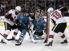 Sharks goalie Aaron Dell stops a shot while teammate Justin Braun (61) tries to shield him from the Senators' Zack Smith, left, and Derick Brassard during the first period.