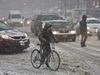 A pedestrian and cyclist join vehicles on Flatbush Avenue during a slushy snowfall in the Brooklyn borough of New York on Thursday, March 5, 2015. Northeasterners are enduring one of the coldest, snowiest seasons in decades. (AP Photo/Bebeto Matthews)