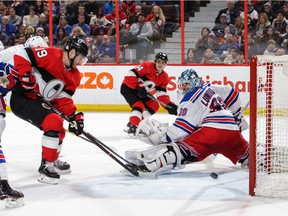 Senators defenceman Mark Borowiecki, middle, watches as centre Derick Brassard tips his pass into the Rangers' net for a goal during the second period of Saturday's game at Canadian Tire Centre.
