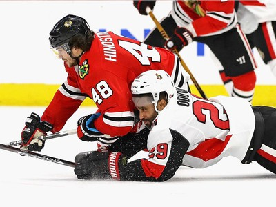 Johnny Oduya and Vinnie Hinostroza hit the ice as they battle for the puck.