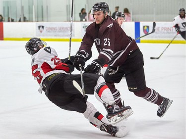 The Ravens' Alexandre Boivin goes down after a collision with uOttawa's Michael Poirier during an Ontario University Athletics playoff game at the Carleton University Ice House on Wednesday, Feb. 14, 2018.