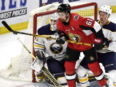 The Senators' Mark Stone tries to deflect the puck in front of Robin Lehner as Casey Nelson looks on.