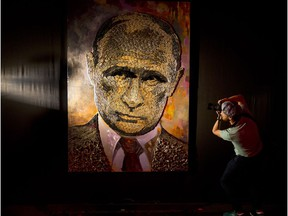 A photographer take a photo of a portrait of Russian President, Vladimir Putin, made by Ukrainian artist Dasha Marchenko, out of cartridge cases, during a presentation in an art gallery in Kiev, Ukraine, Tuesday, Aug. 25, 2015.