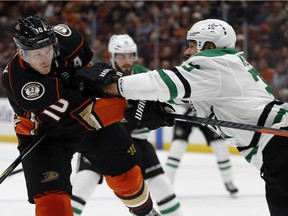 Dallas Stars defenceman Marc Methot, right, checks Anaheim Ducks right wing Corey Perry after Perry shot the puck during the second period of an NHL hockey game in Anaheim, Calif., Wednesday, Feb. 21, 2018.