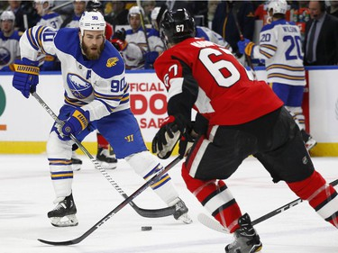 Buffalo Sabres forward Ryan O'Reilly (90) controls the puck in front of Ottawa Senators defenseman Ben Harpur (67) during the first period of an NHL hockey game Wednesday, April 4, 2018, in Buffalo, N.Y.