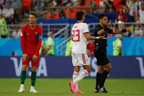 Portugal's Cristiano Ronaldo (left) reacts to receiving a yellow card during Monday's game against Iran. (GETTY IMAGES)