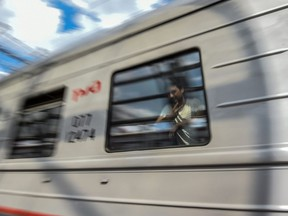 This picture taken on June 20, 2018 shows a fan of the 2018 World Cup tournament riding a train in Saransk, Russia.