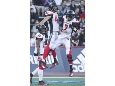 Redblacks fullback Jean-Christophe Beaulieu, left, celebrates with quarterback Trevor Harris after scoring a touchdown against the Alouettes during first-half action on Friday night.