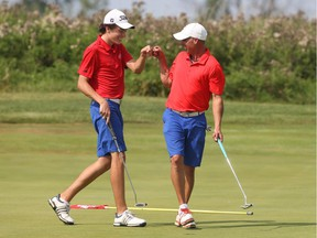 Allen McGee, right, fist-bumps his son Hunter after sinking a birdie putt on the 15th hole of Friday's round. Jean Levac/Postmedia