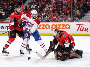 Craig Anderson #41 of the Ottawa Senators makes a save against Phillip Danault #24 of the Montreal Canadiens as Christian Jaros #83 of the Ottawa Senators looks on in the first period at Canadian Tire Centre on October 20, 2018 .