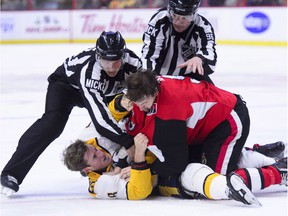 Linemen pull Senators right-winger Bobby Ryan (9) off Predators centre Kyle Turris after their fight during the second period of Monday's game at Canadian Tire Centre.