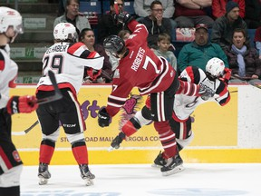 Merrick Rippon of the 67's collides with Storm's Zachary Roberts as Tye Felhaber gets his guard up in Game 4 last night in Guelph.                                               GAR FITZGERALD/PHOTO
