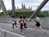 A pace runner leads Hiwot Gebrekidan of Ethiopia, second from left, Gelete Burka of Ethiopia, and Lucas McAneney of Canada across the Alexandra Bridge in front of Parliament Hill during the Ottawa Marathon in Ottawa on Sunday, May 27, 2018. THE CANADIAN PRESS/Justin Tang ORG XMIT: JDT104