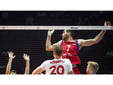 Serbia's Petar Krsmanovic watches the ball careen off a Canadian block at the net.