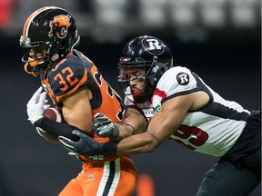 The B.C. Lions' Branden Dozier intercepts a pass intended for the Ottawa Redblacks' Nate Behar in Vancouver on Friday, Sept. 13, 2019.