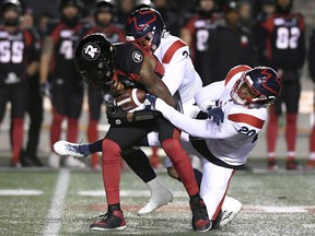 Ottawa Redblacks quarterback Dominique Davis gets sacked by Montreal Alouettes defensive back Patrick Levels and linebacker Boseko Lokombo (20) during first-half CFL football action at TD Place stadium on Friday, Nov. 1, 2019.