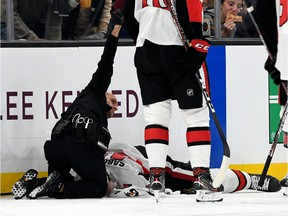A medical staff member calls for assistance while attending to Senators winger Scott Sabourin on the ice in Boston on Saturday evening.
