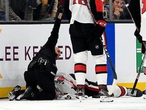 A Senators medical staff member calls for assistance while tending to winger Scott Sabourin, who was knocked unconscious by a collision with Bruins winger David Backes during a game on Nov. 2 in Boston.