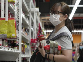 A woman wearing face mask carries a few packets of pasta and bottled sauce at a supermarket after news of the raised outbreak of coronavirus became public people have been panicked to stock up on necessities as on Feb. 9, 2020 in Singapore. (Ore Huiying/Getty Images)