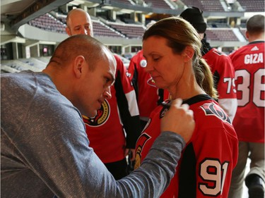Mark Borowiecki signs Debbie Hynes' jersey during a Soldier On event at the Canadian Tire Centre in Ottawa, February 03, 2020.  In partnership with the Canadian Forces' Soldier On Program, the Senators Alumni will host a two-day camp at Canadian Tire Centre in support of ill and injured veterans beginning Monday morning. On Monday, Feb. 3, a group of ill and injured veterans from the Canadian Forces (CF) Soldier On Program will arrive at Canadian Tire Centre for a two-day camp with the Senators Alumni.  Photo by Jean Levac/Postmedia News assignment 133187