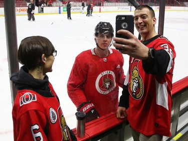Stephen Giza takes a selfie with Mike Reilly of the Ottawa Senators as Jessica Dajko (L) looks on during a Soldier On event at the Canadian Tire Centre in Ottawa, February 03, 2020.  In partnership with the Canadian Forces' Soldier On Program, the Senators Alumni will host a two-day camp at Canadian Tire Centre in support of ill and injured veterans beginning Monday morning. On Monday, Feb. 3, a group of ill and injured veterans from the Canadian Forces (CF) Soldier On Program will arrive at Canadian Tire Centre for a two-day camp with the Senators Alumni.