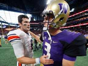 Jarrett Stidham of the Auburn Tigers converses with Jake Browning of the Washington Huskies after their 21-16 win at Mercedes-Benz Stadium on September 1, 2018 in Atlanta, Georgia.