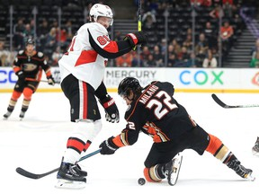 Ron Hainsey of the Ottawa Senators battles Sonny Milano of the Anaheim Ducks for a loose puck during the first period of a game at Honda Center on Tuesday in Anaheim, California.