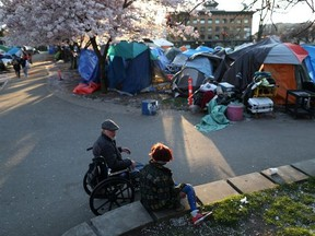 """People sit near a homeless encampment at Oppenheimer Park as the local health unit has started prescribing a """"safe supply"""" of narcotic alternatives to combat overdoses due to poisonous additives and to support addicts and the homeless into practicing social distancing to help slow the spread of coronavirus disease (COVID-19) in the Downtown Eastside of Vancouver, April 7, 2020."""