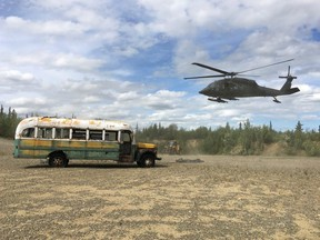 """An Alaska National Guard helicopter hovers near """"Bus 142"""" after it was deposted on the ground west of Healy, Alaska, June 18, 2020."""