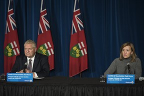 Deputy Premier and Minister of Health Christine Elliott responds to a question as Ontario Premier Doug Ford listens during a press conference at Queen's Park in Toronto on Friday, December 11, 2020.