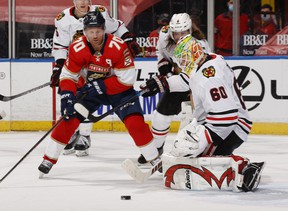 Goaltender Collin Delia #60 of the Chicago Blackhawks turns away the shot by Patric Hornqvist #70 of the Florida Panthers at the BB&T Center on January 17, 2021 in Sunrise, Florida.