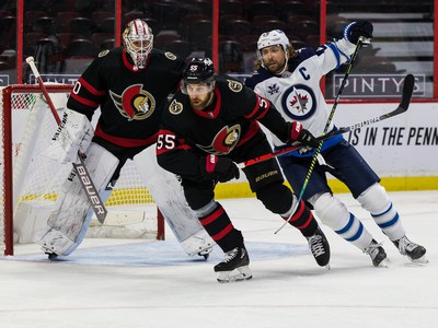 Senators defenceman Braydon Coburn battles with Jets right-winger Blake Wheeler in front of netminder Matt Murray (30) during second-period play.