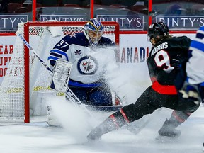 Jets goaltender Connor Hellebuyck makes a save against Senators centre Josh Norris during the first period of Thursday's game at Canadian Tire Centre.