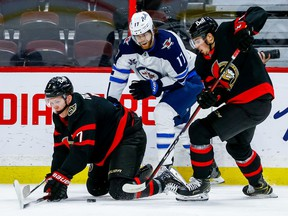 Senators left-winger Brady Tkachuk and right-winger Drake Batherson get the puck away from Jets left-winger Adam Lowry in the first period at the Canadian Tire Centre on Thursday.