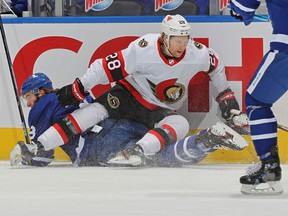Connor Brown #28 of the Ottawa Senators forces Justin Holl #3 of the Toronto Maple Leafs to the ice at Scotiabank Arena on February 17, 2021 in Toronto, Ontario, Canada.