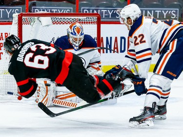 Oilers goaltender Mikko Koskinen makes a save on Senators right-winger Evgenii Dadonov as defenceman Tyson Barrie trips him in the first period.
