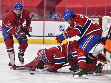 Canadiens goaltender Carey Price reaches to stop the puck as teammates Shea Weber, left, and Ben Chiarot defend the crease against the Senators during the first period.