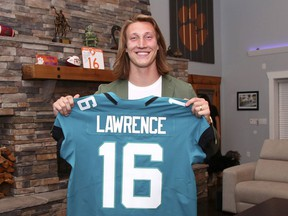 A handout photo provided by the National Football League, quarterback shows Trevor Lawrence with a Jacksonville Jaguars jersey after they made him the No. 1 pick in the draft on Thursday night.