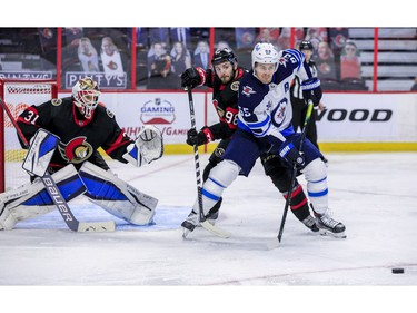 Ottawa Senators defenceman Victor Mete (98) checks Winnipeg Jets centre Mark Scheifele (55) in front of goaltender Anton Forsberg during second period NHL action at the Canadian Tire Centre.
