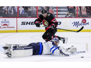 -OTTAWA- April 12,2021. Ottawa Senators right wing Evgenii Dadonov (63) gets poke-checked by Winnipeg Jets goaltender Connor Hellebuyck (37) during third period NHL action at the Canadian Tire Centre. ERROL MCGIHON/Postmedia